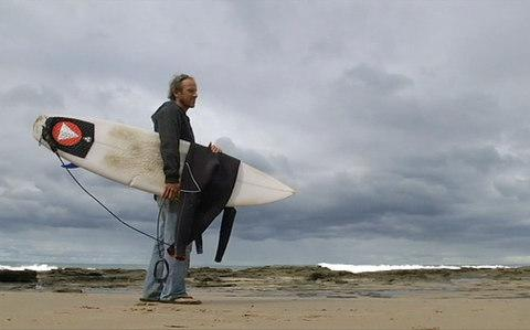 Marcel Brunder holds his board as he looks out to sea after being attacked while surfing - Credit: ABC via AP