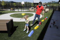 In this May 27, 2020 photo, Aaron Rainboth, a teacher at the Frederickson KinderCare daycare center in Tacoma, Wash., wears a mask as he takes part in a balance exercise with a child during an outdoor play period. In a world weary of the coronavirus, many working parents with young children are now struggling with the decision on when or how they'll be comfortable returning to their child care providers. Frederickson KinderCare, which has been open throughout the pandemic to care for children of essential workers, removed carpets and spaced out tables and chairs as part of their measures to control the spread of the coronavirus. (AP Photo/Ted S. Warren)