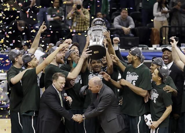 Michigan State players celebrate with the championship trophy after defeating Michigan 69-55 in an NCAA college basketball game in the championship of the Big Ten Conference tournament on Sunday, March 16, 2014, in Indianapolis. (AP Photo/AJ Mast)
