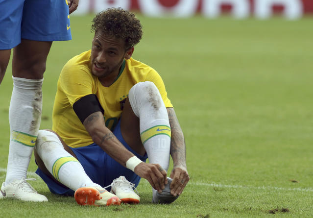 Brazil's Neymar holding his foot after during a friendly soccer match between Austria and Brazil at the Ernst Happel Stadium in Vienna, Austria, Sunday, June 10, 2018. (AP Photo/Ronald Zak)