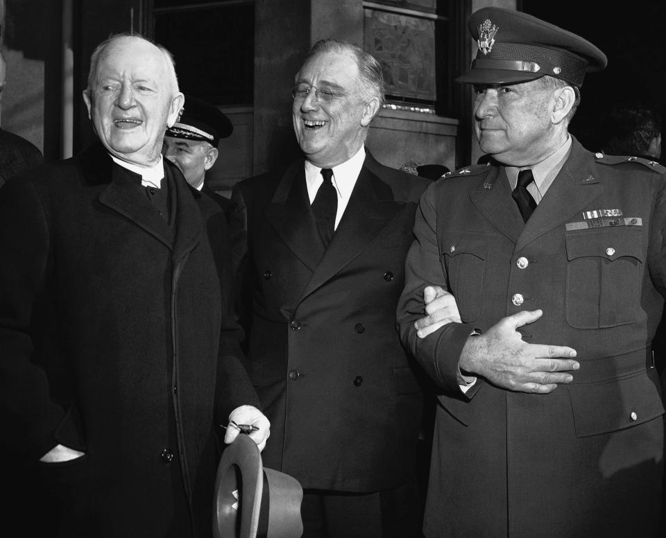 FILE - In this March 4, 1942 file photo, President Franklin Roosevelt leaves after prayer services at St. John's Episcopal Church in Washington, following his custom of attending church on each anniversary of his first inauguration on March 4, 1933. As he left the church he stopped to talk with the Rev. Endicott Peabody, left, headmaster emeritus of Groton school. At right is Major General Edwin M. Watson, presidential secretary and military aide. (AP Photo)
