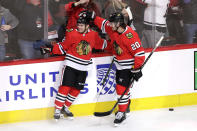 Chicago Blackhawks left wing Alex DeBrincat, left, celebrates with left wing Brandon Saad after scoring the winning goal against the Nashville Predators during the overtime period of an NHL hockey game in Chicago, Friday, Feb. 21, 2020. (AP Photo/Nam Y. Huh)
