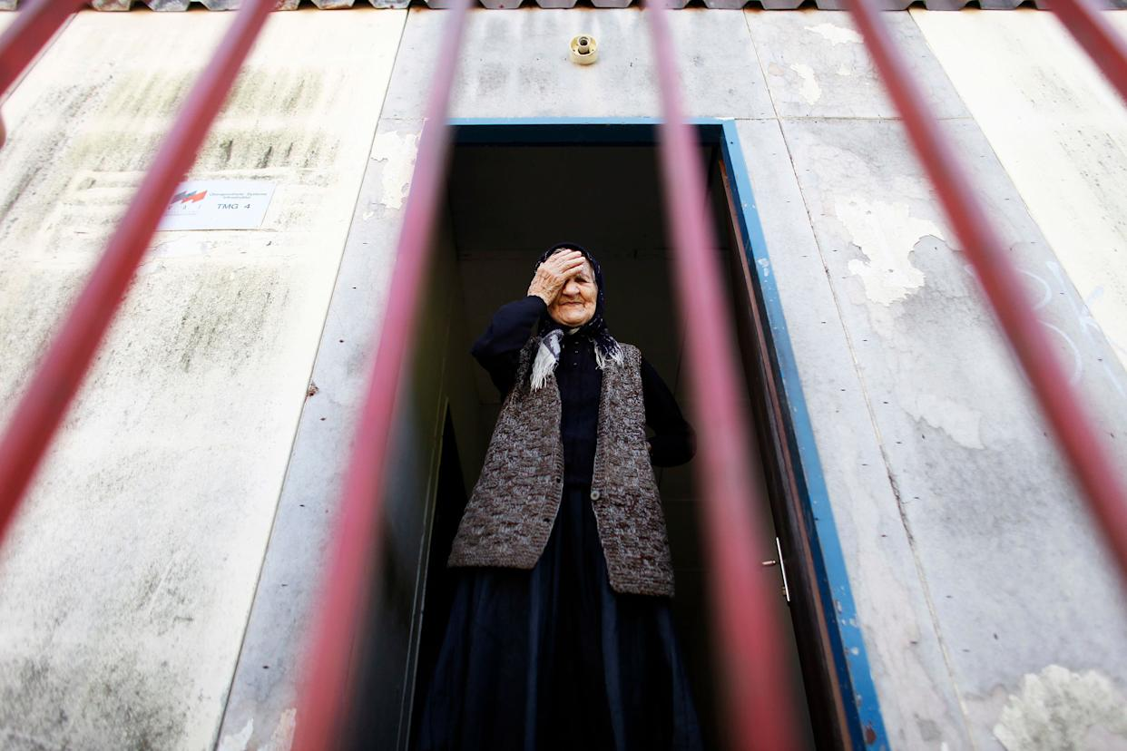 Milena Gavric, a 90-year-old Bosnian Serb refugee, holds her head as she waits for a U.N. delegation to visit her collective center in Srebrenica August 26, 2009.