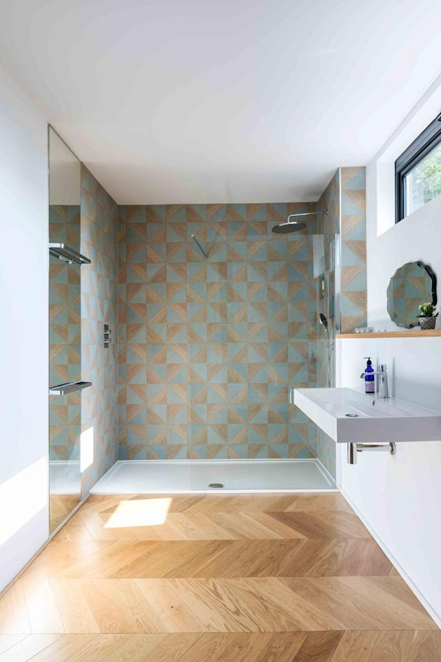 "<p>Geometric oak and blue glazed tiles from Mandarin Stone create a striking and unusual feature wall in this walk-in shower area. Bathroom goals...<br></p><p><a class=""body-btn-link"" href=""https://www.housebeautiful.com/uk/renovate/build/a22510902/forever-family-home-contemporary-new-build-broadstairs-kent/"" target=""_blank"">TAKE A TOUR</a></p>"