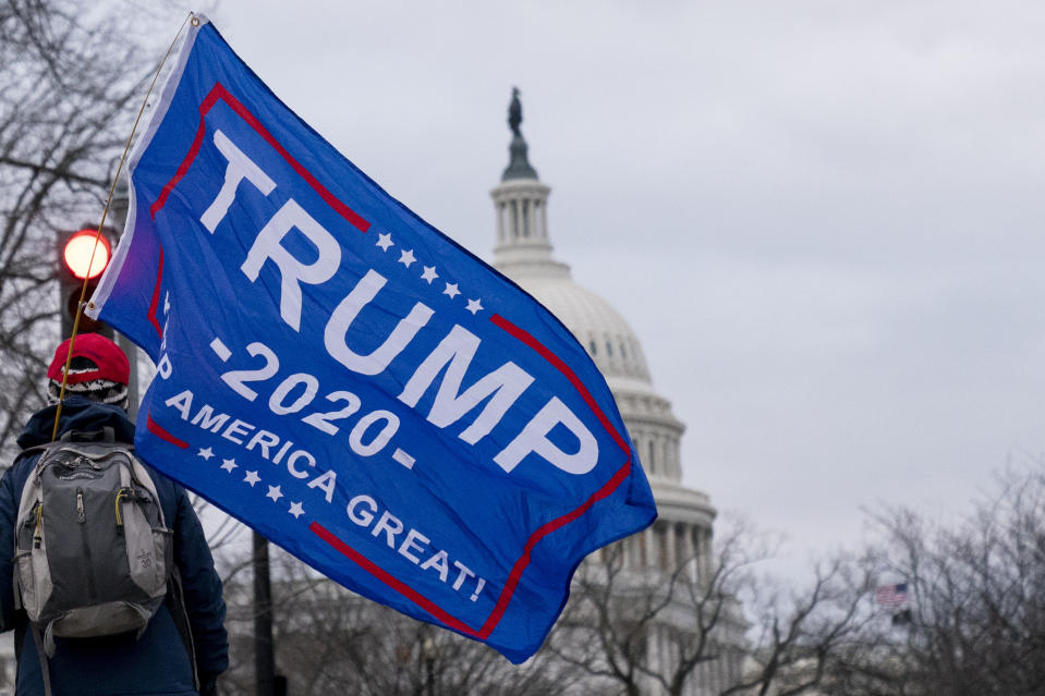 A Trump supporter walks past the Dome of the Capitol Building in Washington, Wednesday, Jan. 6, 2021. (AP Photo/Andrew Harnik)