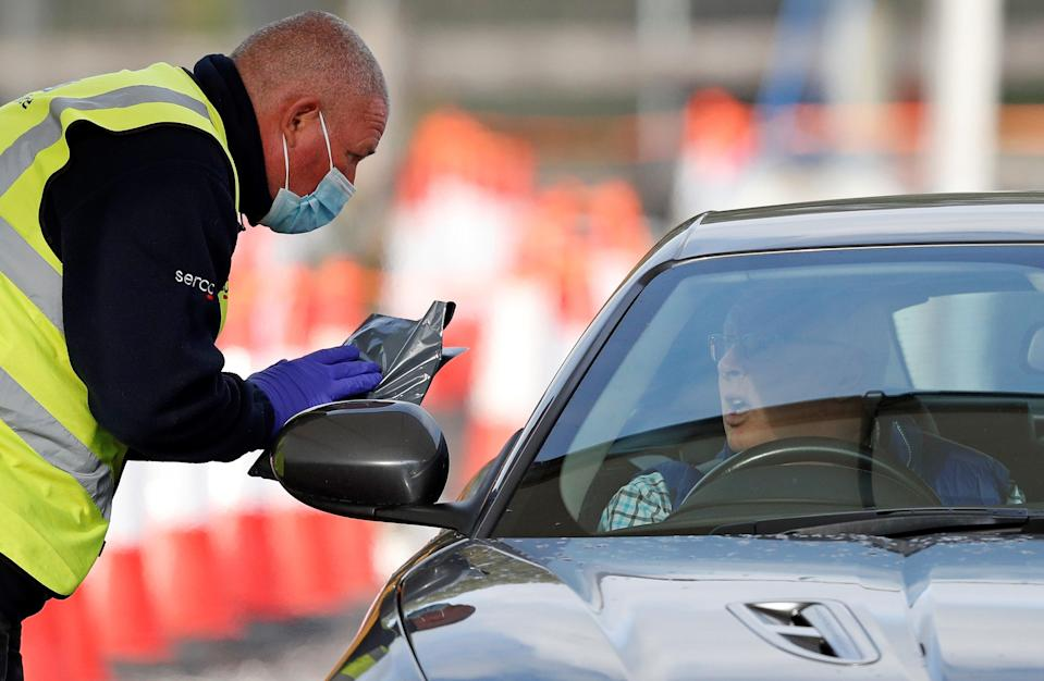 Serco workers help test people at a drive-in test site (AFP via Getty Images)
