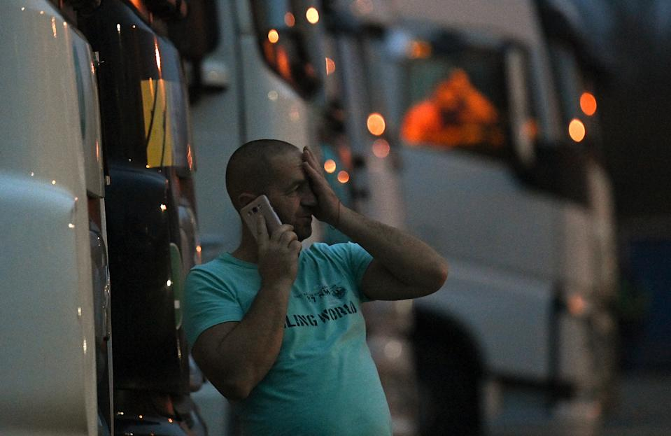 A driver of a freight lorry talk son his phone as he stands outside his cab parked at a truck stop off the M20 leading to Dover, near Folkestone in Kent, south east England on December 22, 2020, after France closed its borders to accompanied freight arriving from the UK due to the rapid spread of a new coronavirus strain. - The British government said Tuesday it was considering tests for truckers as part of talks with French authorities to allow the resumption of freight traffic suspended due to a new coronavirus strain. Britain was plunged into fresh crisis last week with the emergence of a fresh strain of the virus, which is believed to be up to 70 percent more transmissible than other forms. (Photo by JUSTIN TALLIS / AFP) (Photo by JUSTIN TALLIS/AFP via Getty Images)