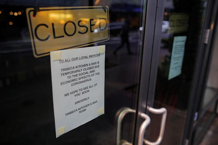 A sign announcing that Tribeca Kitchen and Bar is closed because of the coronavirus outbreak is displayed on a door in Seattle, Washington, U.S., March 13, 2020. REUTERS/Brian Snyder