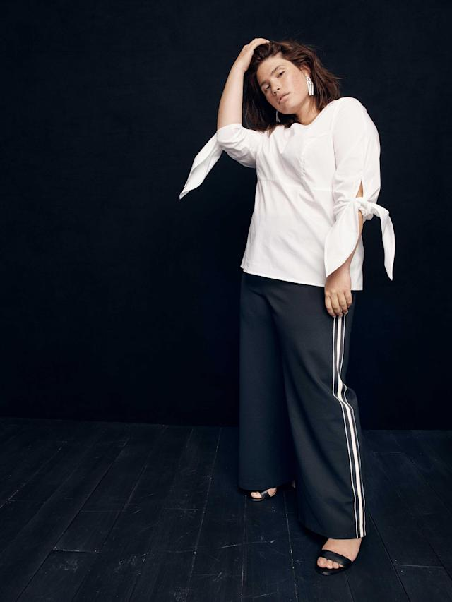 Model wears white blouse and racer stripe trousers from the new size-inclusive J.Crew collection with Universal Standard. (Photo: Courtesy of J.Crew)