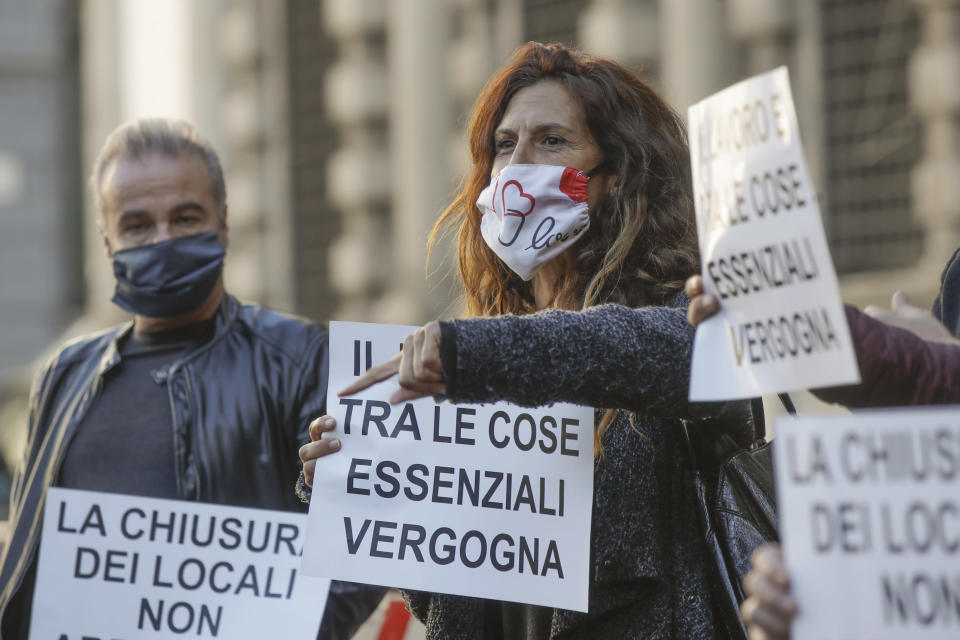 "Restaurants and bars owners and dealers hold signs reading in Italian ""Work is between essential things, shame on you"" as they stage a protest against the government restriction measures to curb the spread of COVID-19, in front of the Milan city hall, Italy, Tuesday, Oct. 27, 2020. Italy's leader has imposed at least a month of new restrictions to fight rising coronavirus infections, shutting down gyms, pools and movie theaters and putting an early curfew on cafes and restaurants. (AP Photo/Luca Bruno)"