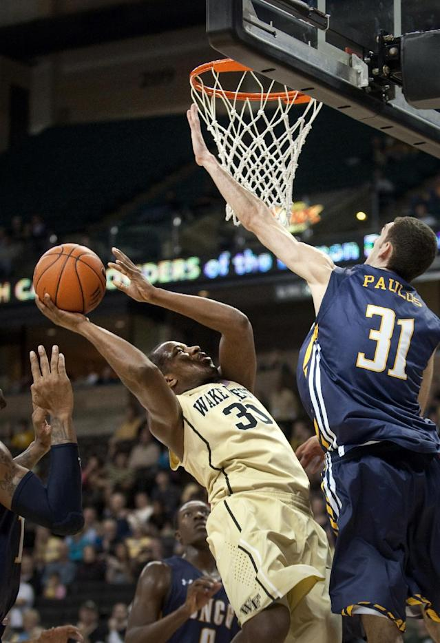 Wake Forest's Travis McKie, left, goes up for a shot as UNC Greensboro's Nicholas Paulos defends during an NCAA college basketball game, Saturday, Dec. 21, 2013, in Winston-Salem, N.C. (AP Photo/Winston-Salem Journal, Lauren Carroll)