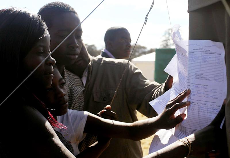 Voters look at posted results outside a polling station in Harare Thursday, Aug. 1, 2013 President Robert Mugabe's ZANU PF party said Thursday, that it has withdrawn an unauthorized message on its Twitter feed claiming a resounding victory in the country's national elections. (AP Photo)