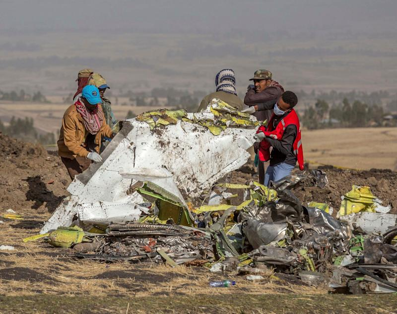 Workers clear debris from the scene of an Ethiopian Airlines crash near Bishoftu, or Debre Zeit, Ethiopia, on Monday. (AP Photo/Mulugeta Ayene)