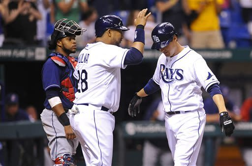 Cleveland Indians catcher Carlos Santana, left, looks on as Tampa Bay Rays Kelly Johnson, right, and Jose Molina celebrate Johnson's two-run home run during the fourth inning of a baseball game on Saturday, April 6, 2013, in St. Petersburg, Fla. (AP Photo/Brian Blanco)