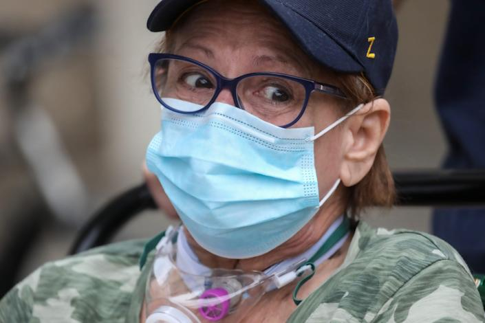 Deanna Hair, 67, of Ann Arbor becomes emotional after talking about her battle with COVID-19 and being hospitalized at the University of Michigan hospital for 196 days and finally being discharged as family and friends cheer her on, Thursday, Oct. 15, 2020.