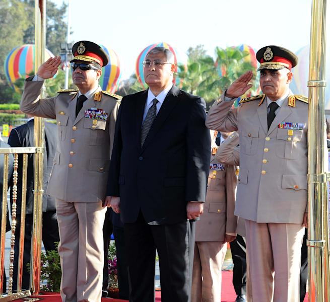 In this photo released by the Egyptian Presidency, Egypt's interim President Adly Mansour, center, Defense Minister Abdel-Fatah el-Sissi, left, and other officials visit the Tomb of the Unknown Soldier and President Anwar Sadat's memorial as part of celebrations marking the 40th anniversary of the start of the 1973 Middle East war in which Egyptian forces made initial gains against Israel, Saturday, Oct. 5, 2013. Egypt's army is on high alert ahead of expected mass demonstrations by supporters of ousted Islamist President Mohammed Morsi timed to coincide with annual celebrations honoring the military, a combination many fear will lead to a new round of violence. (AP Photo/Egyptian Presidency)
