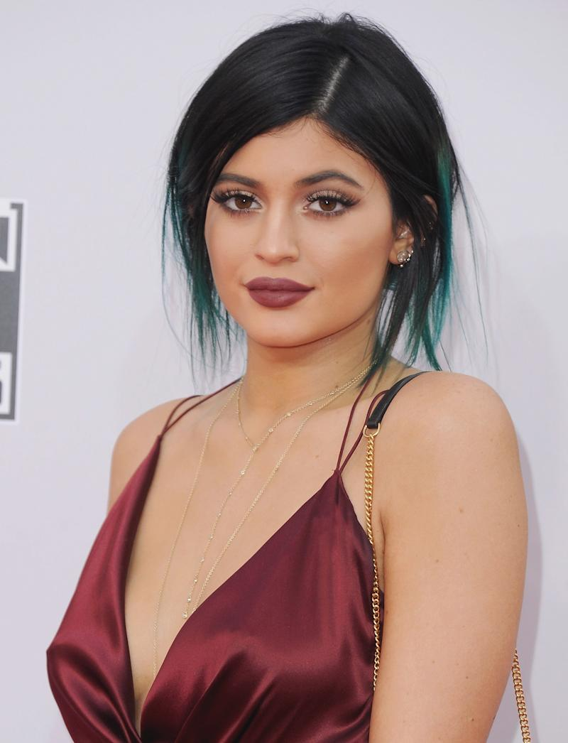 Keeping her turquoise blue highlights, Jenner wears a tousled low bun with a matte mauve lip at the 2014 American Music Awards.