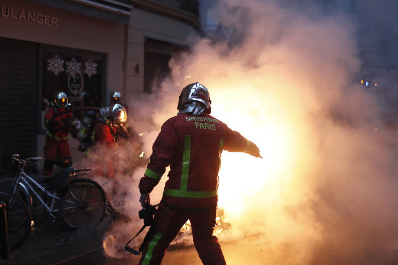 Emergency workers attempt to quash flash fires across Paris on Saturday after riots flared once more.