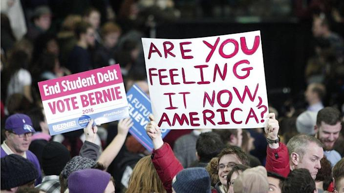 Supporters of U.S. Senator and Democratic Presidential Candidate Bernie Sanders hold signs at Sanders' first campaign rally in Michigan at Eastern Michigan University February 15th, 2016 in Ypsilanti, Michigan