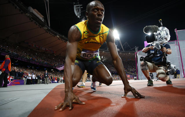 Jamaica's Usain Bolt crouches on the track after winning the men's 100m final during the London 2012 Olympic Games at the Olympic Stadium August 5, 2012. Bolt came first ahead of compatriot Yohan Blake who finished second and Justin Gatlin of the U.S. who placed third. REUTERS/Kai Pfaffenbach (BRITAIN - Tags: SPORT ATHLETICS OLYMPICS)