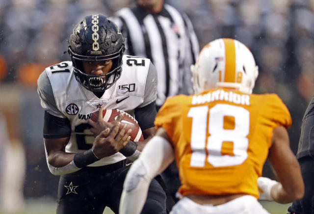 Vanderbilt running back Keyon Brooks (21) runs for yardage as he's defended by Tennessee defensive back Nigel Warrior (18) in the first half of an NCAA college football game Saturday, Nov. 30, 2019, in Knoxville, Tenn. (AP Photo/Wade Payne)