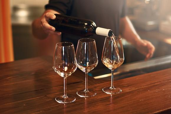 sommelier filling three wine glasses with white wine