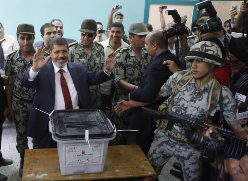"""FILE - In this Saturday, June 16, 2012 file photo, Egyptian presidential candidate Mohammed Morsi waves after he casts his vote at a polling station in Zagazig, 63 miles (100 kilometers) northeast of Cairo, Egypt. A statement on the Egyptian president's office's Twitter account has quoted Mohammed Morsi as calling military measures """"a full coup."""" The denouncement was posted shortly after the Egyptian military announced it was ousting Morsi, who was Egypt's first freely elected leader but drew ire with his Islamist leanings. The military says it has replaced him with the chief justice of the Supreme constitutional Court, called for early presidential election and suspended the Islamist-backed constitution. (AP Photo/Amr Nabil, File)"""