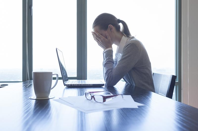 A woman with her head in her hands sits at an office desk with a laptop on it.