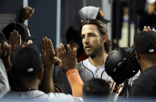 San Francisco Giants' Madison Bumgarner celebrates his two-run home run with teammates in the dugout during the sixth inning of a baseball game against the Los Angeles Dodgers, Tuesday, April 2, 2019, in Los Angeles. (AP Photo/Marcio Jose Sanchez)