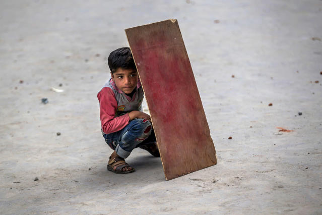 <p>A Kashmiri boy shields himself with plywood from stones and glass marbles during a clash between Indian policemen and protesters during a protest in Srinagar, Indian controlled Kashmir, May 19, 2017. Government forces fired tear gas during clashes with Kashmiri protesters in the Indian-controlled portion of Kashmir after Friday prayers called by separatist leaders against the continuous detention of woman separatist leader Asiya Adrabi, chairman of Dukhtaran-e-Millat, or Daughters of the Nation. They also demand release of all political prisoners from Indian prisons. (Photo: Dar Yasin/AP) </p>