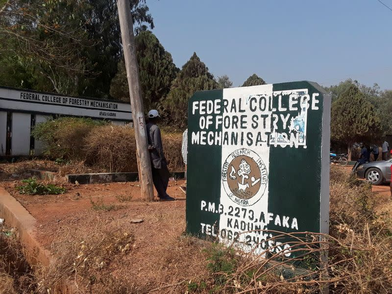 Man rests on a pole beside the signage of the Federal College of Forestry Mechanization where gunmen abducted students, in Kaduna