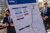 A poster depicting transportation plans is visible as Transportation Secretary Pete Buttigieg, left, and Rep. Don Beyer, D-Va., right, depart following a news conference to announce the expansion of commuter rail in Virginia at the Amtrak and Virginia Railway Express (VRE) Alexandria Station, Tuesday, March 30, 2021, in Alexandria, Va. (AP Photo/Andrew Harnik)