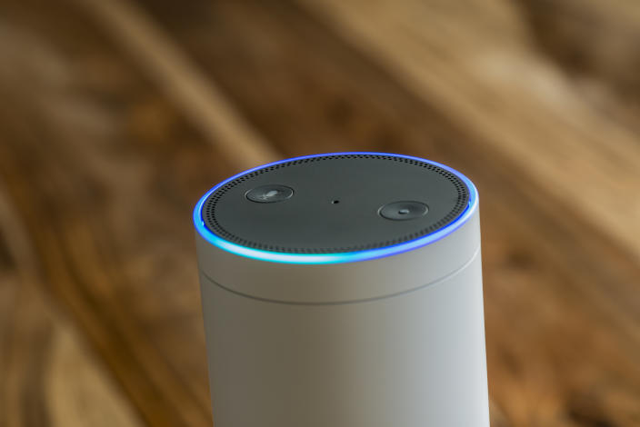 MUENSTER - JANUARY 27, 2018: White Amazon Echo Plus, Alexa Voice Service activated recognition system photographed on wooden table in living room.