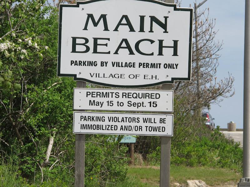 """In this photograph taken Monday, May, 13, 2013, a sign lists rules and regulations to enter Main Beach in East Hampton, N.Y., stands ready to greet summer visitors. Main Beach is number one on the 2013 list of Top 10 Beaches produced annually by coastal expert Stephen P. Leatherman, also known as """"Dr. Beach,"""" director of Florida International University's Laboratory for Coastal Research.  (AP Photo/Frank Eltman)"""