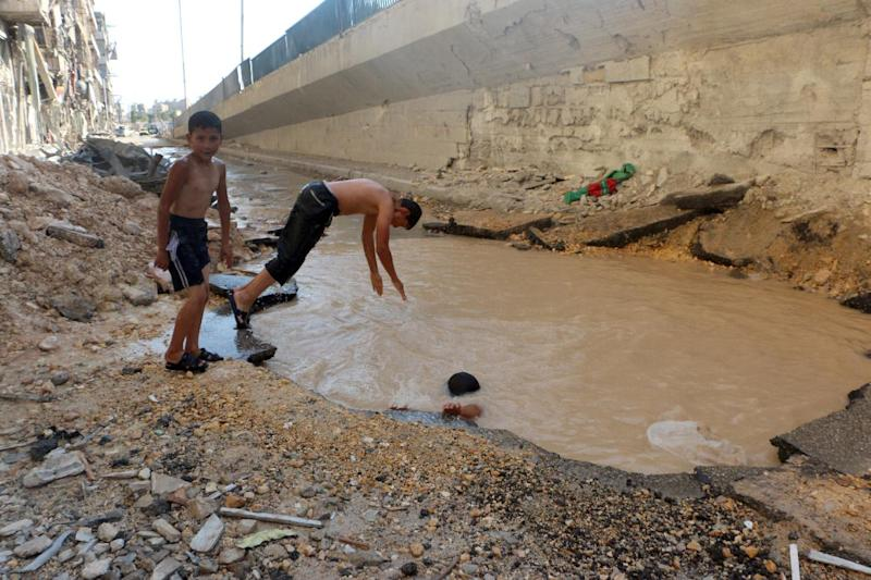 Syrian children play in a bomb crater flooded with water from a broken main in the northern city of Aleppo, on July 10, 2014 (AFP Photo/Fadi al-Halabi)