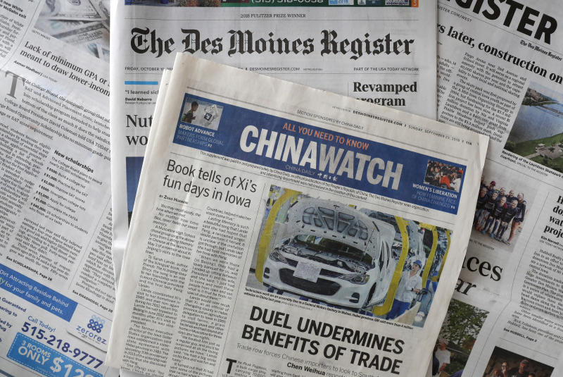This Friday, Oct. 19, 2018, photo shows a copy of the four-page advertising section Chinawatch along with a copy of The Des Moines Register in Des Moines, Iowa. China's propaganda machine has taken aim at American soybean farmers as part of its high-stakes trade war with the Trump administration. The publication last month of the four-page advertising section in the Register opened a new battle line in China's effort to break the administration's resolve. (AP Photo/Charlie Neibergall)