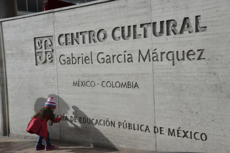 A girl touches the sign outside the Gabriel Garcia Marquez cultural center in downtown Bogota, Colombia, Thursday, April 17, 2014. The Colombian Nobel laureate Gabriel Garcia Marquez died in Mexico City on Thursday. (AP Photo/Diana Sanchez)