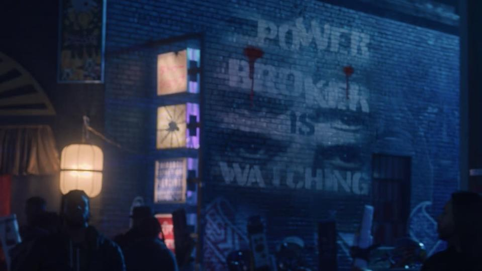 """A brick wall in Madripoor that says, """"Power Broker is Watching"""" with two sets of eyes between the words, from Marvel's The Falcon and the Winter Soldier."""
