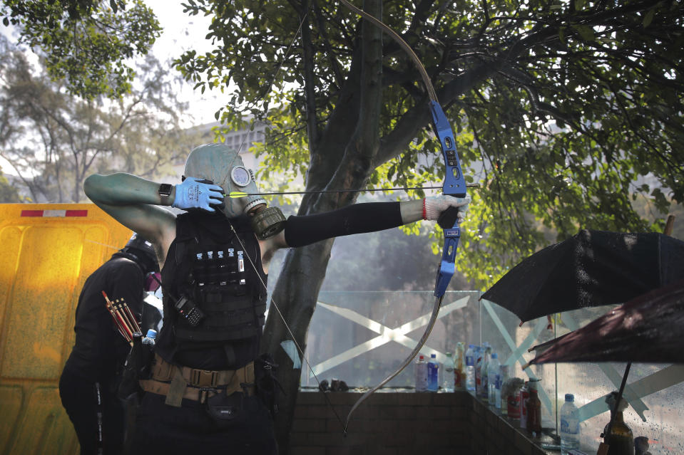 A protestor prepares to fire a bow and arrow during a confrontation with police at the Hong Kong Polytechnic University in Hong Kong, Sunday, Nov. 17, 2019. (AP Photo/Kin Cheung)