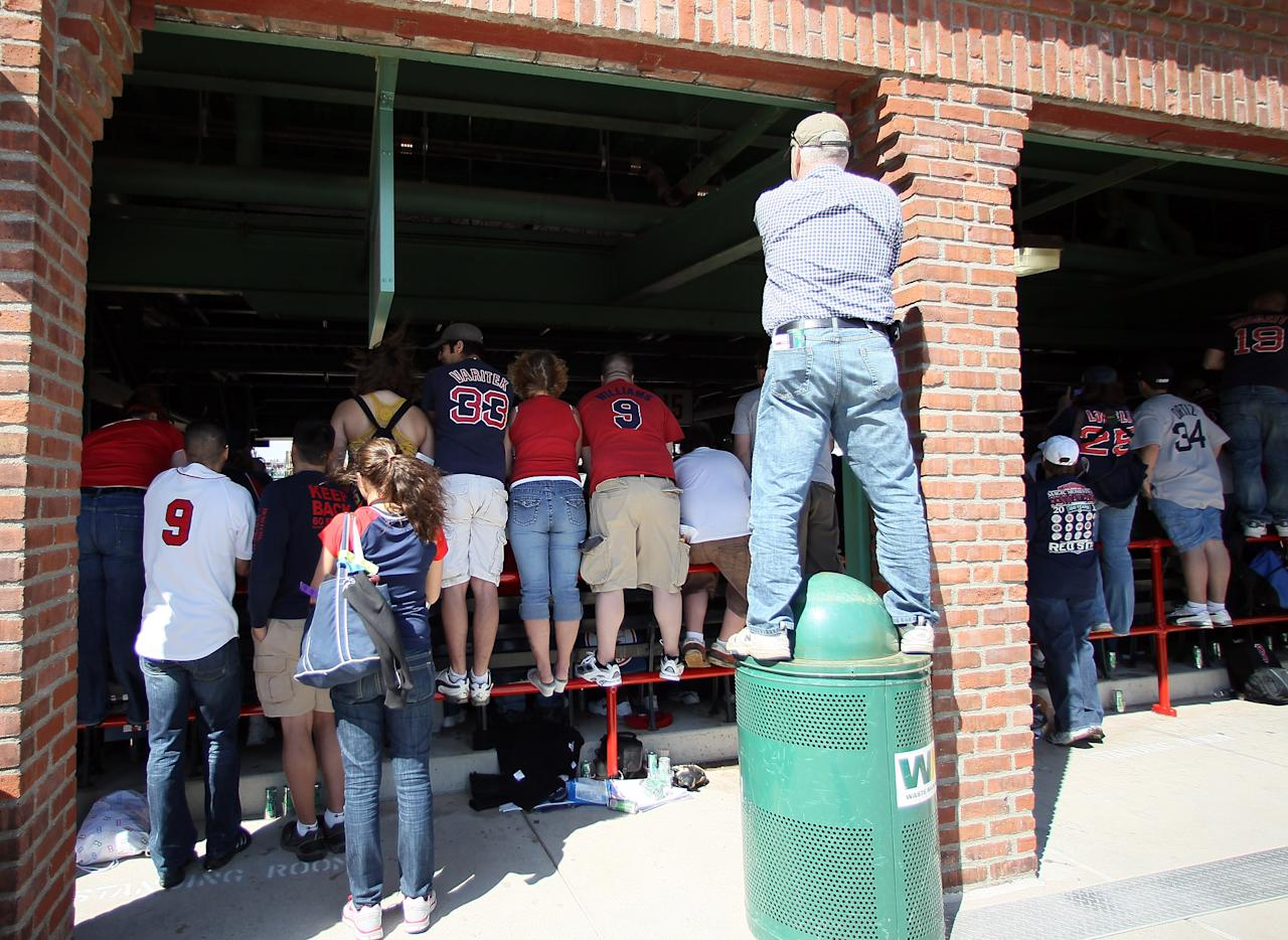 BOSTON, MA - APRIL 20:  Standing room only fans try to get a good view of the 100 Year celebration ceremony before the game between the New York Yankees and the Boston Red Sox on April 20, 2012 at Fenway Park in Boston, Massachusetts. Today marks the 100 year anniversary of the ball park's opening.  (Photo by Elsa/Getty Images)
