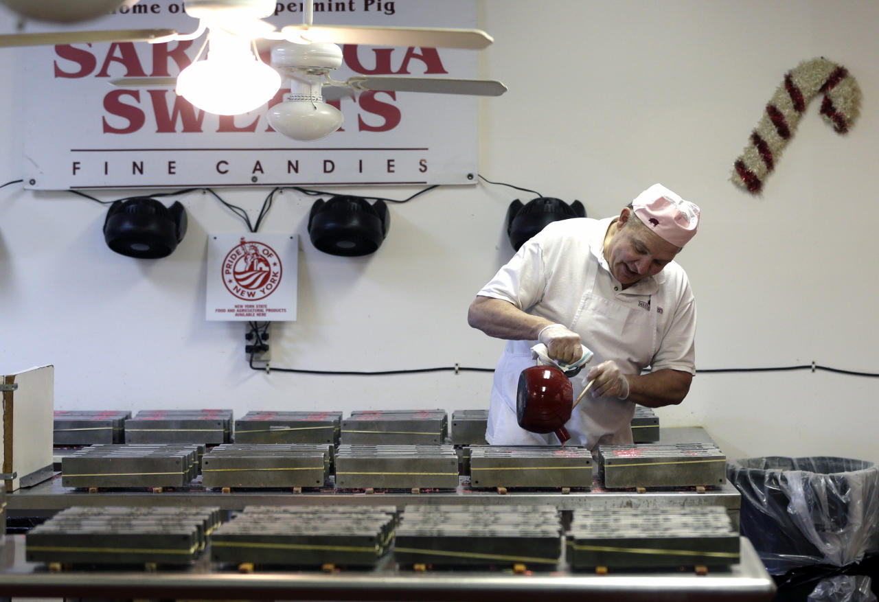 In this Dec. 6, 2012, photo, Mike Fitzgerald pours hot peppermint mixture into a mold while making peppermint pigs at his Saratoga Sweets store in Halfmoon, N.Y. A holiday tradition in upstate New York has a peppermint twist: pig-shaped hard candies are sold with little metal hammers to be smashed at Christmas. (AP Photo/Mike Groll)