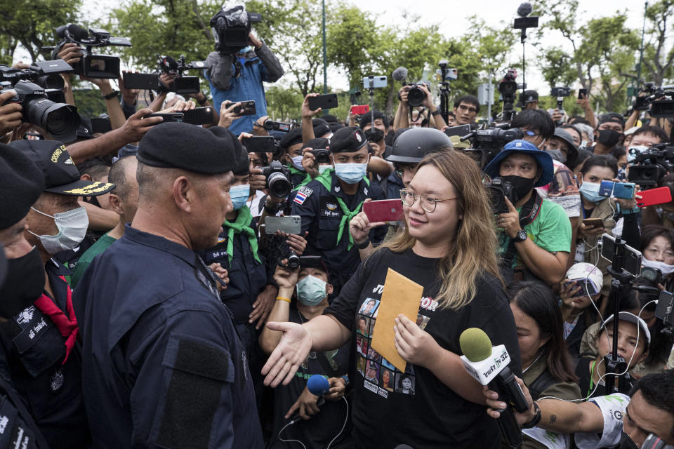 FILE - In this Sept. 20, 2020, file photo, one of the pro-democracy student leaders negotiates with police officials as they march on road during a protest in Bangkok, Thailand. Fed up with an archaic educational system and enraged by the military's efforts to keep control over their nation, a student-led campaign has shaken Thailand's ruling establishment with the most significant campaign for political change in years. (AP Photo/Wason Wanichakorn, File)