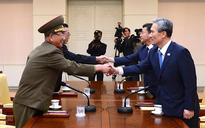 South Korean National Security Director, Kim Kwan-jin, right, and Unification Minister Hong Yong-pyo, second from right, shake hands with Hwang Pyong So in 2015 - The South Korean Unification Minisry