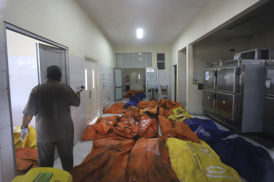 Staff members stand among body bags containing the bodies of the victims of a prison fire at the local hospital's morgue in Tangerang on the outskirts of Jakarta, Indonesia, Wednesday, Sept. 8, 2021. A massive fire raged through an overcrowded prison near Indonesia's capital early Wednesday, killing a number of inmates. (AP Photo)
