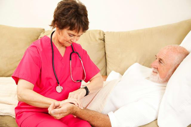 BP1776 Home health nurse taking the pulse of an elderly patient. home; healthcare; nurse; senior; elderly; care; medical; man; wNew life insurance policy from Vitality Life allows you to access payout early to help pay for care