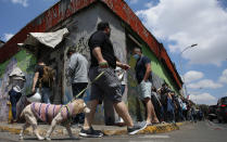 A man walks with his dog past people lining up for their turn to vote during a referendum to decide whether the country should replace its 40-year-old constitution, written during the last dictatorship, in Santiago, Chile, Sunday, Oct. 25, 2020. (AP Photo/Luis Hidalgo)