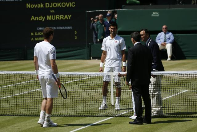 Serbia's Novak Djokovic and Great Britain's Andy Murray watch as the coin toss is performed before their Men's Singles Final during day thirteen of the Wimbledon Championships at The All England Lawn Tennis and Croquet Club, Wimbledon.