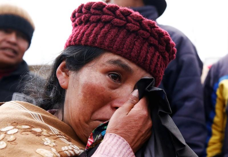 A woman cries as she lines up to get gas canisters next to blocked petrol plant of Senkata in El Alto outskirts of La Paz