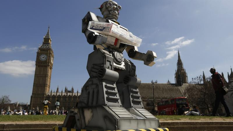A robot is pictured in front of the Houses of Parliament and Westminster Abbey as part of the Campaign to Stop Killer Robots in London April 23, 2013. Robots with the ability to attack targets without any human intervention must be banned before they are even developed for use in a battlefield, campaigners urged on Tuesday. REUTERS/Luke MacGregor (BRITAIN - Tags: SCIENCE TECHNOLOGY MILITARY CONFLICT POLITICS CIVIL UNREST) - LM1E94N172P01