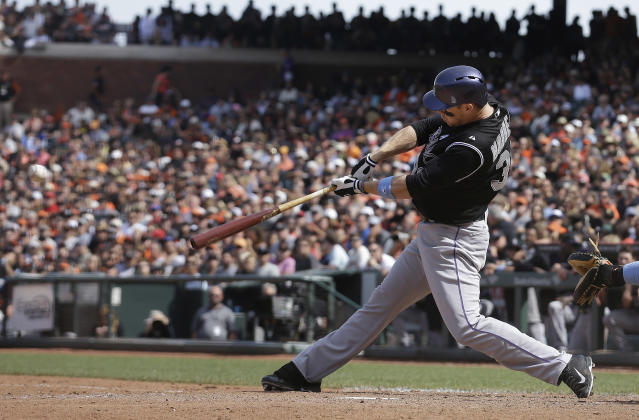 Colorado Rockies' Justin Morneau hits a two-run double off of San Francisco Giants pitcher Javier Lopez during the eighth inning of a baseball game in San Francisco, Sunday, June 15, 2014. (AP Photo/Jeff Chiu)
